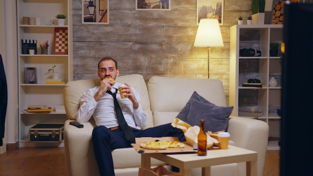 Zmęczony biznesmen w garniturze siedzi na kanapie śmiejąc się przed telewizorem po ciężkim dniu w pracy.