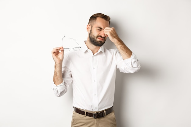 Zmęczony biznesmen zdejmuje okulary i przeciera oczy, stoi wyczerpany