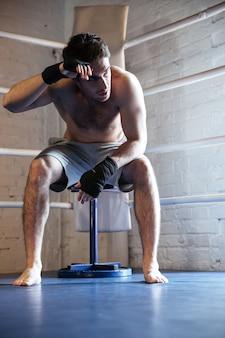 Zmęczony bokser ociera pot siedząc na ringu