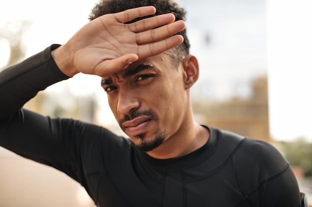 Zmęczony brodaty sportowiec dotyka twarzy