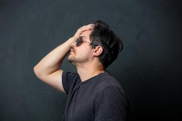 Zmęczony brunet mężczyzna w czarnej koszulce i okularach przeciwsłonecznych na ciemnej ścianie