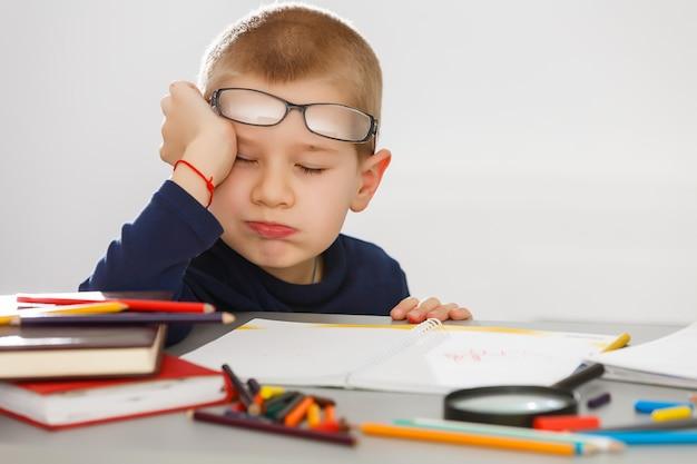 Zmęczony chłopiec odrabiania lekcji