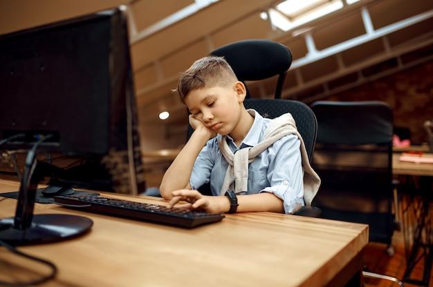 Zmęczony chłopiec siedzi przy aparacie, mały bloger. blogowanie dzieci w domowym studio, media społecznościowe dla młodych odbiorców, transmisje internetowe online, kreatywne hobby