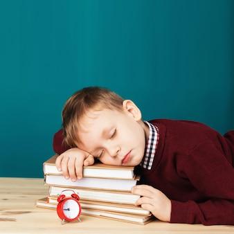 Zmęczony chłopiec śpi na książkach. mały student śpiący na podręcznikach