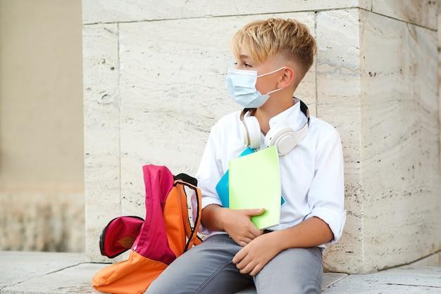 Zmęczony chłopiec w masce ochronnej po lekcjach.