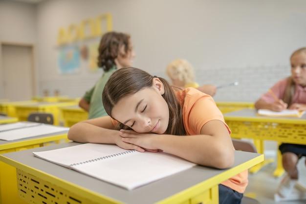 Zmęczony. ciemnowłosa dziewczyna w pomarańczowej koszulce śpi na biurku