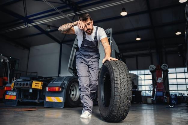 Zmęczony ciężko pracujący mechanik toczy oponę, aby zmienić ją na ciężarówce. jest w garażu firmy importowo-eksportowej.