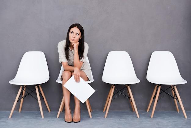 Zmęczony czekaniem. znudzona młoda kobieta trzymająca papier i odwracająca wzrok siedząc na krześle na szarym tle