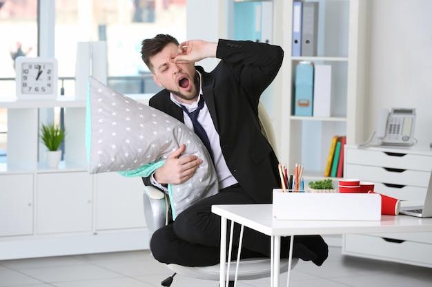 Zmęczony człowiek biznesu z poduszką na krześle w miejscu pracy w biurze