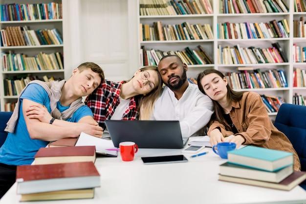 Zmęczony czterech uczniów rasy mieszanej ma wiele do nauki w bibliotece, opierając się i śpiąc przy stole