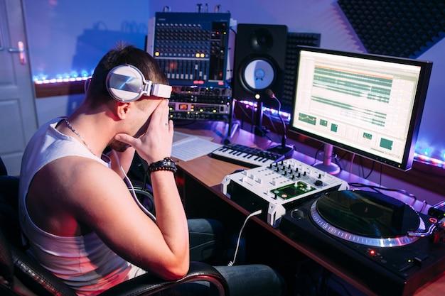 Zmęczony dj zakrywający twarz rękami w studio nagrań.