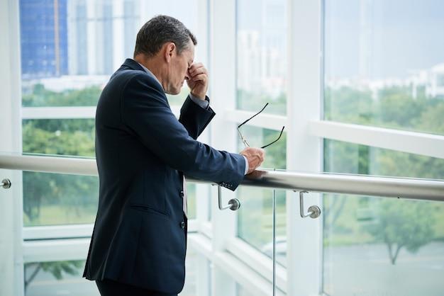 Zmęczony dojrzały biznesmen w garniturze stojący przy balustradzie biurowego balkonu i trzymający okulary podczas masowania mostka nosa