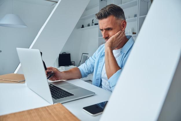 Zmęczony dojrzały mężczyzna pracujący na laptopie siedząc przy biurku