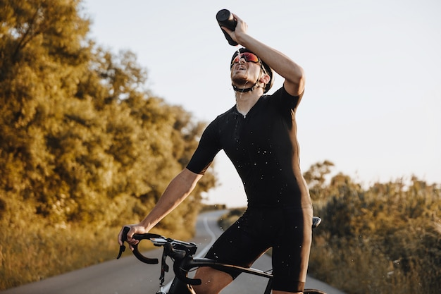 Zmęczony dojrzały mężczyzna w odzieży sportowej, kasku ochronnym i lustrzanych okularach pije słodką wodę stojąc na brukowanej drodze ze swoim rowerem.