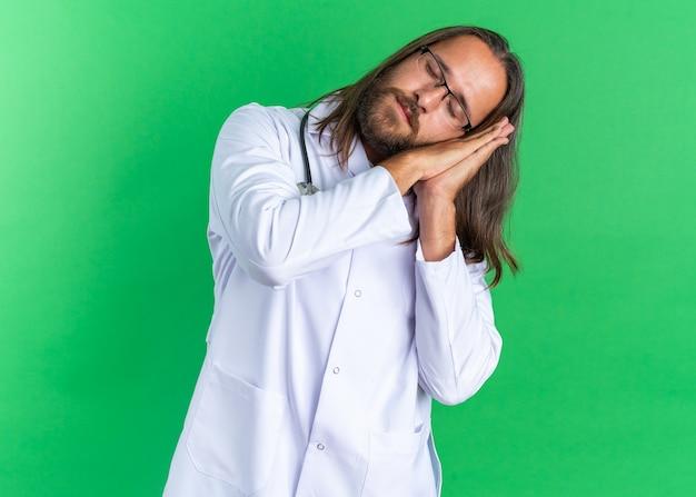 Zmęczony dorosły lekarz mężczyzna ubrany w szatę medyczną i stetoskop w okularach, wykonujący gest snu z zamkniętymi oczami