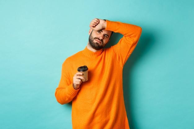 Zmęczony dorosły mężczyzna robi sobie przerwę w pracy i pije kawę, ociera pot z czoła i wygląda na wyczerpanego, stojącego w pomarańczowym swetrze na turkusowym tle.