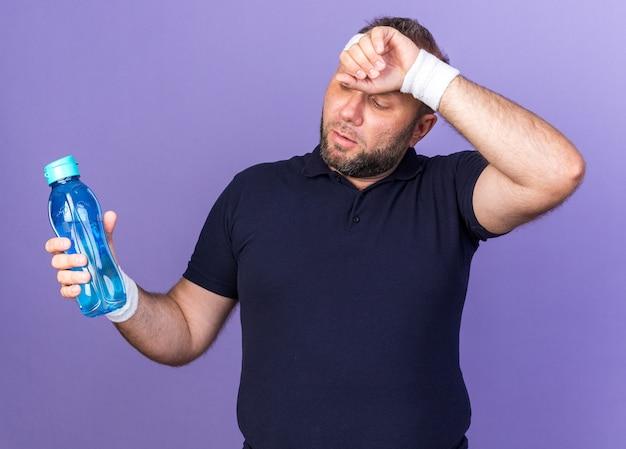 Zmęczony dorosły słowiański sportowy mężczyzna noszący opaskę na głowę i opaski, kładący rękę na czole i trzymający butelkę wody odizolowaną na fioletowej ścianie z kopią miejsca