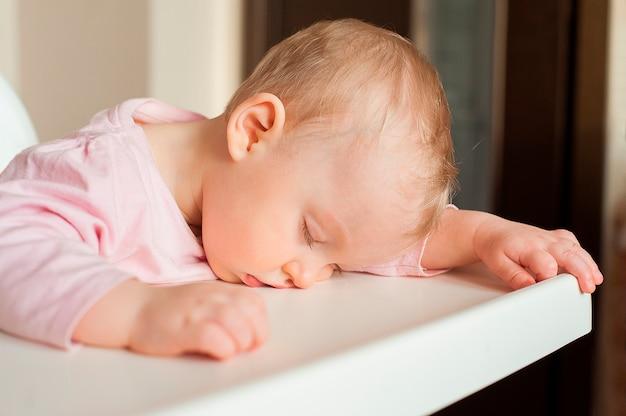Zmęczony dziecko śpi w krzesełku po obiedzie. śliczna dziewczynka przejadać się i spadać uśpiony