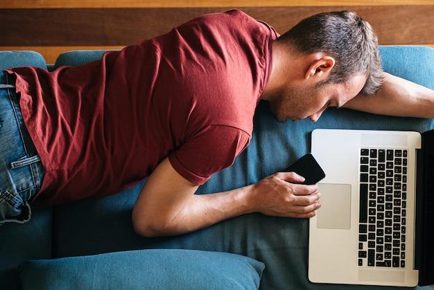 Zmęczony facet śpi na kanapie z urządzeniami w domu