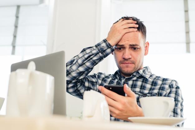 Zmęczony freelancer korzysta z telefonu komórkowego podczas pracy w kawiarni