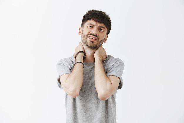 Zmęczony i chory przystojny facet pozuje przy białej ścianie