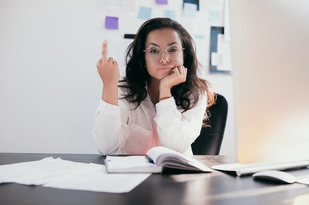 Zmęczony i niegrzeczny pracownik młoda kobieta pokazuje środkowy palec do kamery