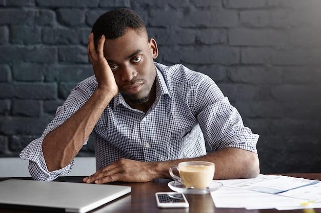 Zmęczony i nieszczęśliwy młody menedżer z bólem głowy, zmęczonym i przepracowanym wyglądem