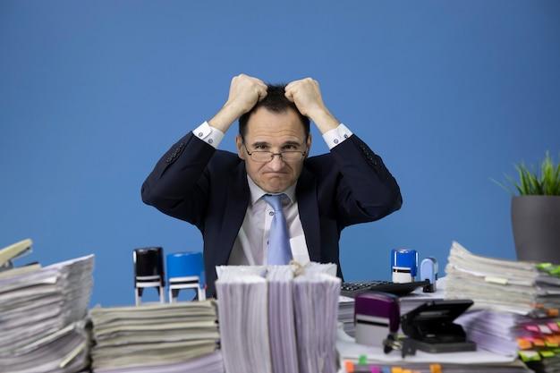 Zmęczony i przepracowany biznesmen wyrywa sobie włosy zestresowany przy biurku wypełnionym papierami