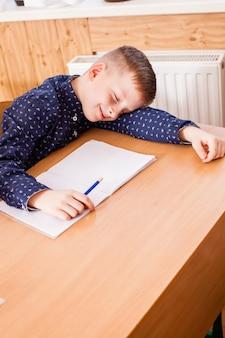Zmęczony i śpiący chłopak podczas lekcji podstawówki. nudna edukacja