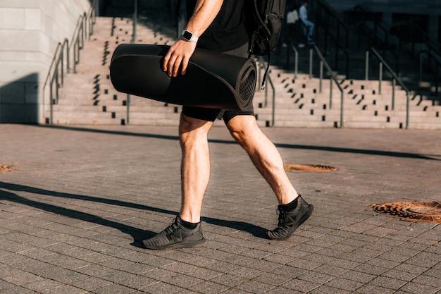 Zmęczony i zadowolony sportowiec wraca do domu po porannym treningu. wytnij widok nóg wysportowanego mężczyzny. koncepcja sportu miejskiego. człowiek chodzący na ulicy i trzymając rolowaną matę do jogi.