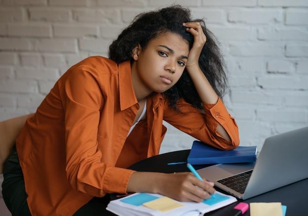 Zmęczony i zestresowany student studiuje, uczy się języka, egzamin. smutny freelancer przekroczył termin, wielozadaniowość