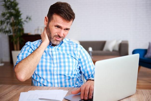 Zmęczony i zmartwiony mężczyzna korzystający z laptopa w pracy