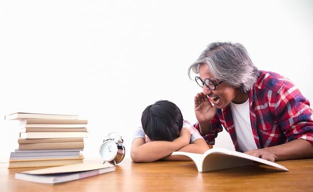 Zmęczony i znudzony chłopiec śpi wśród książek w klasie