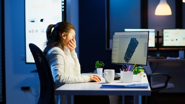 Zmęczony inżynier konstruktor analizujący nowy prototyp modelu 3d rośliny ziewającej w godzinach nadliczbowych. pracownica przemysłowa studiująca pomysł turbiny na komputerze, pokazująca oprogramowanie cad na wyświetlaczu urządzenia