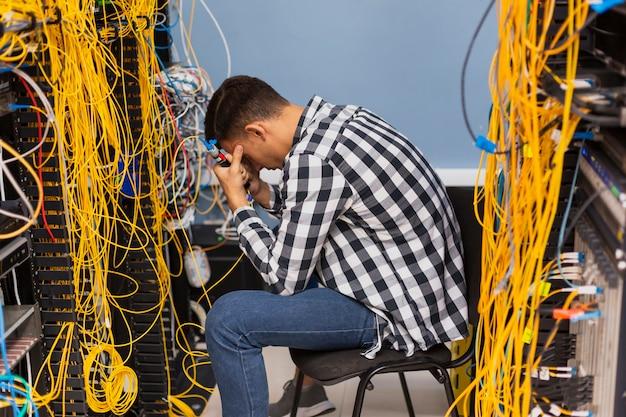 Zmęczony inżynier sieci siedzi na serwerowni