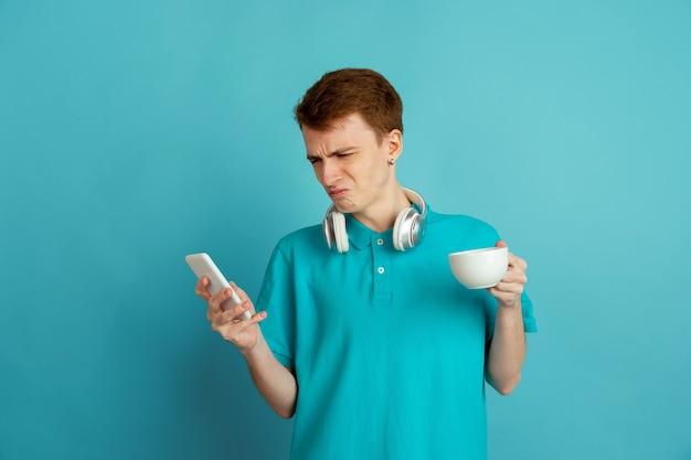 Zmęczony kawą i telefonem. kaukaski portret młodego mężczyzny na białym tle na niebieskiej ścianie, monochromatyczne. piękny męski model. pojęcie ludzkich emocji, wyraz twarzy,