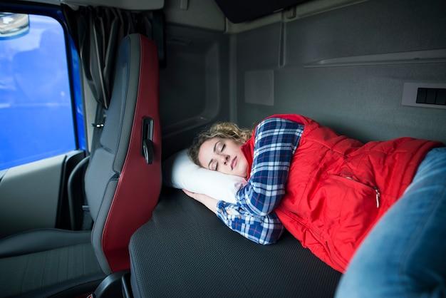 Zmęczony kierowca ciężarówki śpi w kabinie swojej ciężarówki z powodu pokonywania długich dystansów i przepracowania