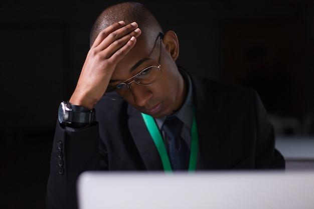 Zmęczony kierownik pracuje w biurze późno w nocy