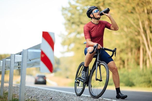 Zmęczony kolarz szosowy w czarnym kasku i lustrzanych okularach orzeźwiający zimną wodą po długiej porannej jeździe