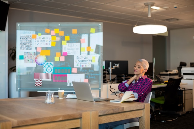 Zmęczony kreatywnych bizneswoman siedzi na biurku w biurze