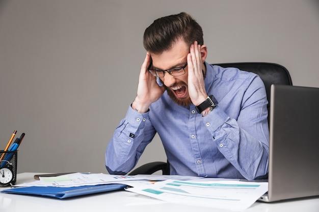 Zmęczony krzyczący brodaty elegancki mężczyzna w okularach trzymający się za głowę siedząc przy stole w biurze