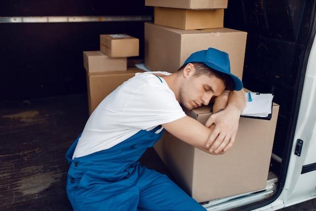 Zmęczony ładowacz w mundurze śpiącym na stosie paczek w samochodzie, firma kurierska. mężczyzna stojący przy kartonowych paczkach w pojeździe, mężczyzna dostawy, kurier lub wysyłka