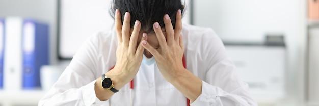 Zmęczony lekarz pochyla głowę w gabinecie po dniu pracy. sytuacje stresujące w ujęciu medycyny