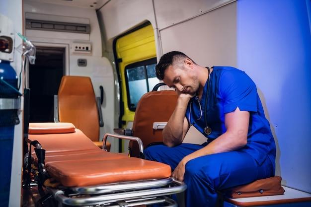 Zmęczony lekarz w niebieskim mundurze czeka na zakończenie zmiany