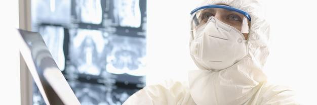 Zmęczony lekarz w ochronnym kombinezonie przeciw dżumie, siedzący na podłodze z rentgenem w rękach w klinice.
