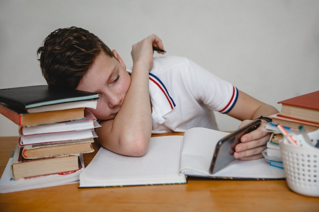 Zmęczony lekcjami nastolatek w domu po podręczniki patrzy na smartfona