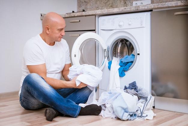 Zmęczony łysy mężczyzna siedzi z brudną bielizną w pralce