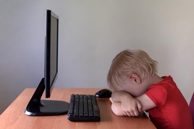 Zmęczony mały blond chłopiec śpi na stole pod monitorem
