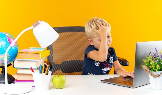Zmęczony mały chłopiec siedzący przy stole z szkolnymi narzędziami używał laptopa, kładąc rękę na głowie
