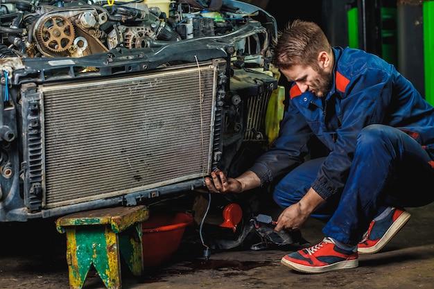Zmęczony mechanik w niebieskim ubraniu ochronnym naprawia chłodnicę samochodową.
